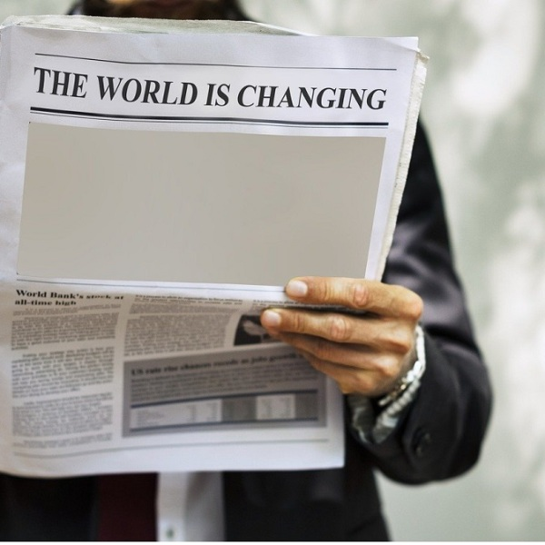"Hombre con un periódico donde se lee: ""The World is changing"""