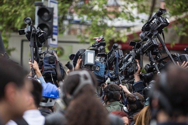 Periodistas en grupo con cámaras y micrófonos